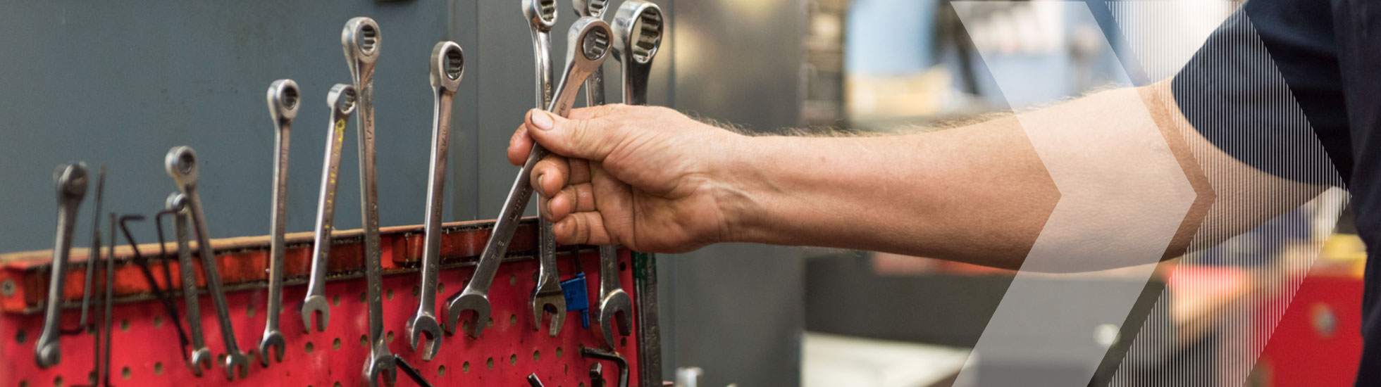 A hand reaching for a wrench in a red toolbox