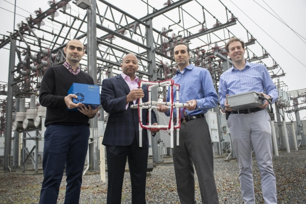 Georgia Tech researchers Tohid Shekari, Raheem Beyah, Morris Cohen, and Lukas Graber hold an antenna and home-built recording equipment for the very low frequency (VLF) radio receiver