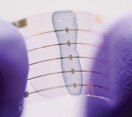 Thumb and finger bending a clear stretchable electronic.