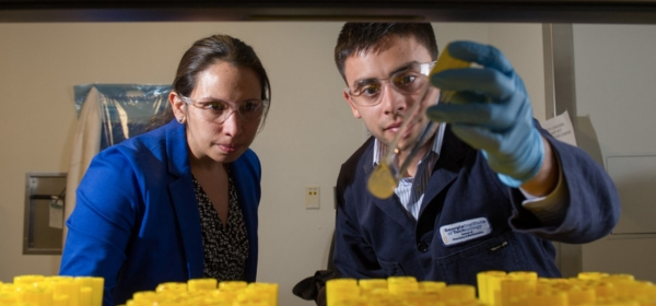 Pamela Peralta Yahya and a student looking at yellow test tube contents